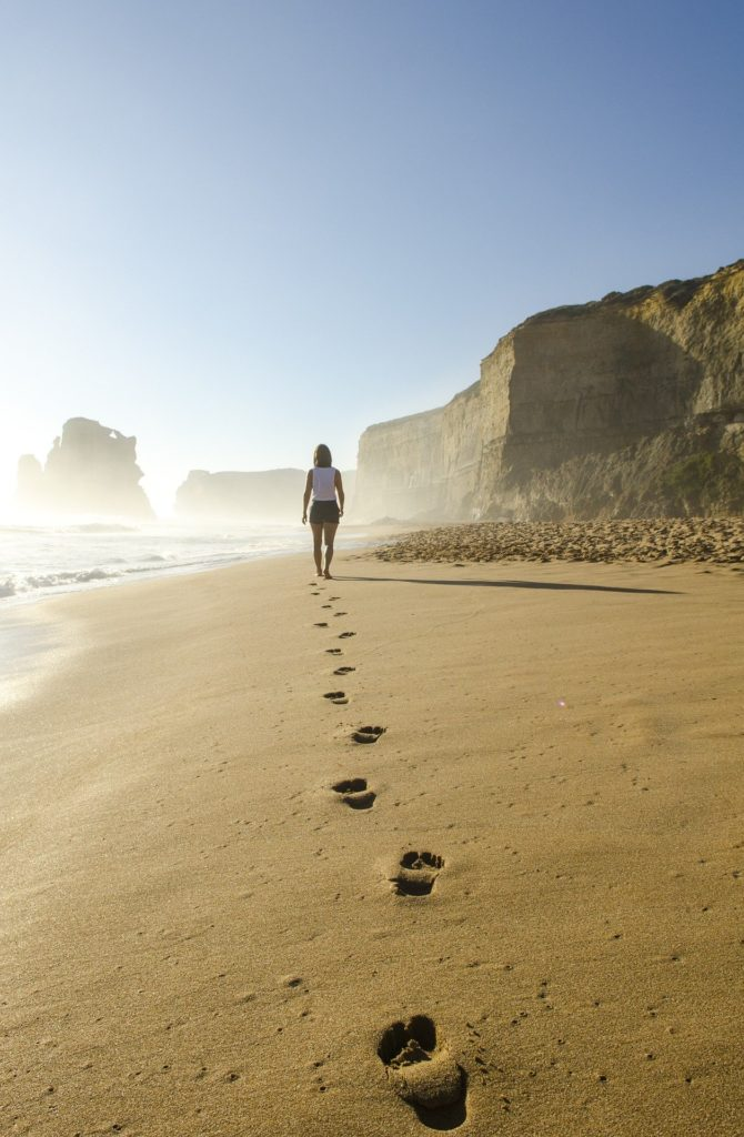 Frau spaziert am Sandstrand